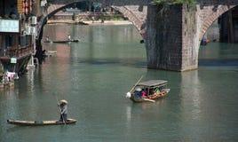 FENGHUANG - 13 de abril: Barcos de madeira com os turistas em Fenghuang Imagem de Stock