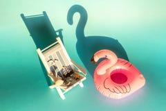 Fenicottero e sedia a sdraio gonfiabili su un fondo blu, partito del galleggiante dello stagno fotografie stock libere da diritti