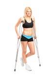 Fenmale novo ferido em muletas Fotos de Stock Royalty Free