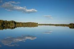Fenn mit hellem blauem Himmel und Wolken reflektierte sich im Wasser Stockfotografie