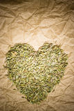 Fennel dill seeds heart shaped on paper surface Royalty Free Stock Photos