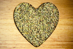 Fennel dill seeds heart shaped on wooden board Royalty Free Stock Photo