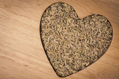 Fennel dill seeds heart shaped on wooden board Stock Photography