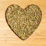 Fennel dill seeds heart shaped on wooden board Stock Images