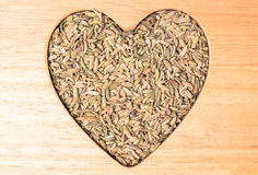 Fennel dill seeds heart shaped on wooden board Royalty Free Stock Images
