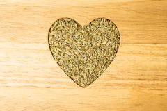Fennel dill seeds heart shaped on wooden board Royalty Free Stock Photos