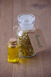 Fennel seeds and a bottle of oil, selective focus on dark wooden Royalty Free Stock Photos