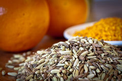 Fennel seeds and dry orange rind. Fennel seeds and dry orange rind with oranges in the background royalty free stock images
