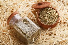 Fennel seeds. In glass jar and wooden bowl on raffia background Royalty Free Stock Images