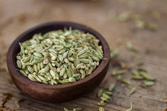 Fennel seeds. In a small wooden bowl on an old wooden table Royalty Free Stock Photos