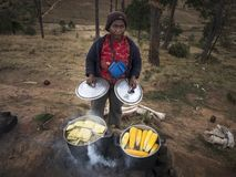 Woman selling cooked corn on the cob, lifting lids of pots royalty free stock photos