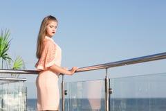 Fenomenalna i wspaniała kobieta na tarasie na niebieskiego nieba tle Dziewczyna jest ubranym różową suknię blisko hałaśliwie morz Fotografia Royalty Free
