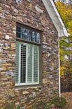 Fenster-Blendenverschlüsse und Steinfassade Stockbild