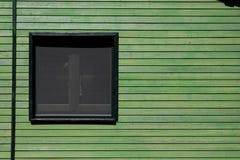 Fenster in der grünen hölzernen Wand Lizenzfreies Stockfoto
