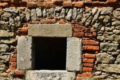 Fenster des dunklen Schwarzen in der Steinwand des antiken Ziegelsteines Lizenzfreie Stockfotografie