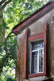 Fenster des gealterten Gebäudes, im Schatten des Baums Lizenzfreie Stockbilder