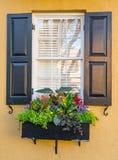 Fenster des Kolonialhauses mit Blumen stockbilder