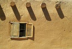 Fenster in einem Gebäude des luftgetrockneten Ziegelsteines Stockfoto