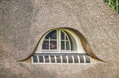 Fenster in einem Strohdach Stockfotos