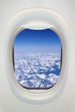 Fenster eines Flugzeuges von innen, Ansicht über schneebedeckte Berge Lizenzfreie Stockfotos