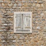 Fenster geschlossen mit hölzernen Fensterläden in der Steinwand lizenzfreies stockbild