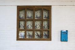 Fenster im alten Haus mit einem Holzrahmen und in einem Briefkasten mit Korrespondenz auf der äußeren Wand 2018 stockfotos