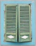 Fenster im grauen/blauen façade mit abgefressenen Fensterläden Stockfotos