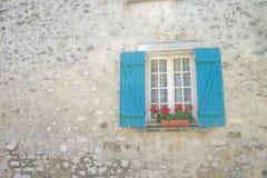 Fenster mit blauen Blendenverschlüssen und roten Blumen Stockfoto