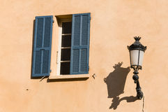 Fenster mit blauen Fensterläden und alter Straßenbeleuchtung Stockfoto