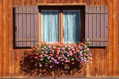 Fenster mit Blumen in hängendem Blumenbehälter Stockfotos