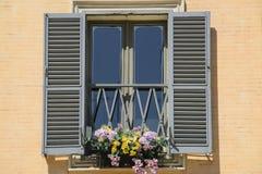 Fenster mit den offenen Fensterläden, verziert mit Blumen, Rom, Italien Lizenzfreie Stockbilder