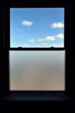 Fenster mit einem blauen Himmel und Wolken Stockbilder