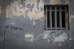 Fenster mit einem Gitter auf einer verfallenen Wand stockfoto