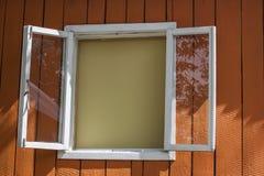 Fenster mit einem weißen Rahmen auf einer orange hölzernen Wand, Hintergrund Stockfoto