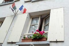 Fenster mit Fensterläden, Flagge von Frankreich und schöne Blumen Lizenzfreies Stockbild