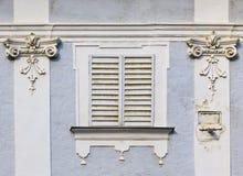 Fenster mit geschlossenen Blendenverschlüssen in einer alten Fassade Stockfotos