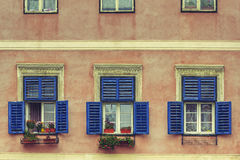 Fenster mit offenen Fensterläden und Blumen Stockfoto