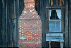Fenster und Kamin in einem alten Schindel-Bauernhaus Stockfotografie
