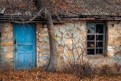Fenster und Tür des alten Hauses unter dem Baum Stockfotos