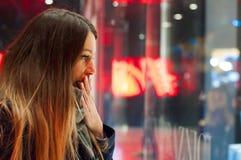 Fenstereinkaufen, Frau, die im Geschäft schaut Lächelnde Frau, die auf das Shopfenster zeigt, bevor stor betreten wird Stockfoto