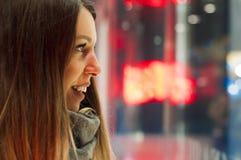 Fenstereinkaufen, Frau, die im Geschäft schaut Lächelnde Frau, die auf das Shopfenster zeigt, bevor stor betreten wird Stockfotografie