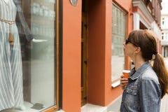 Fenstereinkaufskonzept Junge Frau, die Kleid in einem Shopfenster betrachtet stockfoto