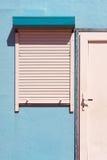 Fensterläden auf dem Hauptschirm und einer weißen Tür Lizenzfreie Stockfotografie