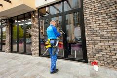 Fensterputzer, der am Errichten im Freien arbeitet Stockfotos
