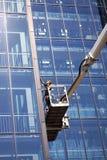 Fensterputzer, die an einem Glasgebäude des modernen hohen Aufstieges arbeiten lizenzfreies stockbild