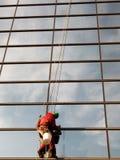 Fensterputzer säubert die Fenster mit einem Lappen zur Helligkeit Stockfotografie
