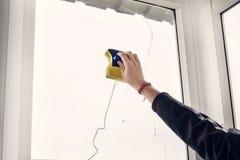 Fensterputzer unter Verwendung einer Gummiwalze, zum eines Fensters, das Fenster mit einer magnetischen Bürste waschend zu wasche Stockfotos