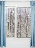 Fenêtre blanche avec les rideaux bleus un jour pluvieux Images libres de droits