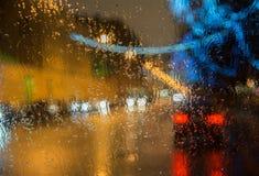 Fenêtre de voitures humide avec le fond de la ville de nuit Image stock