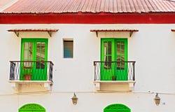 Fenêtres vertes dans la vieille maison Photo stock